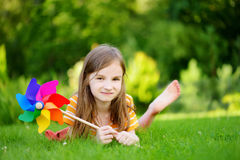 Adorable little girl holding colorful toy pinwheel on summer day Stock Photos