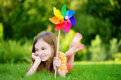 Adorable little girl holding colorful toy pinwheel on summer day Royalty Free Stock Image