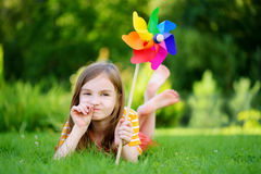 Adorable little girl holding colorful toy pinwheel on sunny summer day Royalty Free Stock Images