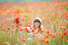 Adorable little girl holding field flowers for her mother in blooming poppy field on beautiful spring day royalty free stock photos