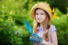 Adorable little girl holding garden tools Royalty Free Stock Image