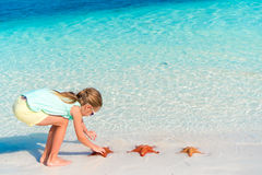 Adorable little girl holding giant red starfish on white empty beach Royalty Free Stock Photo