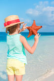 Adorable little girl holding giant red starfish on white empty beach Stock Photography