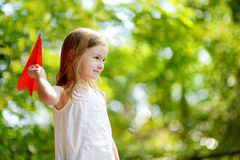 Adorable little girl holding a paper plane Stock Image