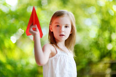 Adorable little girl holding a paper plane Royalty Free Stock Photo