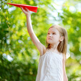 Adorable little girl holding a paper plane Royalty Free Stock Image