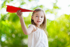 Adorable little girl holding a paper plane Stock Photo