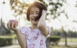 An adorable little girl holding red fresh apple stock photography