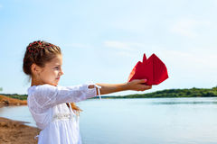 Adorable little girl holding red paper boat Stock Photography