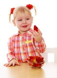 Adorable little girl holding a strawberry sitting Stock Photography