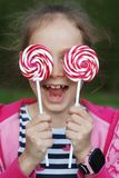 Adorable Little Girl Holding Swirl Lollipop in Hand, Outdoor Summer Portrait over her Yes stock photography