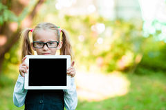 Adorable little girl holding tablet PC outdoors in autumn sunny day Royalty Free Stock Photo