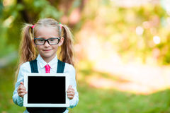 Adorable little girl holding tablet PC outdoors in autumn sunny day Royalty Free Stock Photos