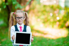 Adorable little girl holding tablet PC outdoors in autumn sunny day Stock Image