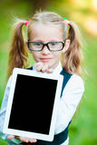 Adorable little girl holding tablet PC outdoors in autumn sunny day Stock Images