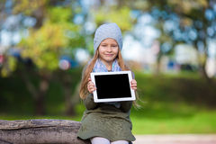 Adorable little girl holding tablet PC outdoors in Royalty Free Stock Images