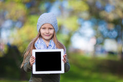 Adorable little girl holding tablet PC outdoors in Stock Photography
