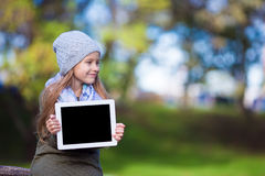 Adorable little girl holding tablet PC outdoors in Stock Images