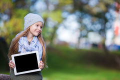 Adorable little girl holding tablet PC outdoors in Royalty Free Stock Image
