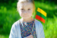 Adorable little girl holding tricolor Lithuanian flag Royalty Free Stock Photography