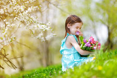 Adorable little girl holding tulips for her mother in blooming cherry garden Stock Images