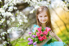 Adorable little girl holding tulips for her mother in cherry garden Stock Photo