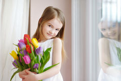 Adorable little girl holding tulips by the window Stock Photo