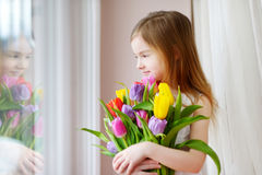 Adorable little girl holding tulips by the window Stock Images