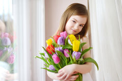 Adorable little girl holding tulips by the window Royalty Free Stock Photos