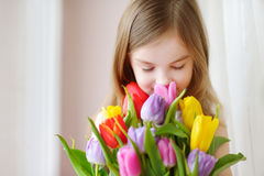 Adorable little girl holding tulips by the window Stock Image
