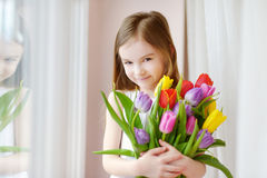 Adorable little girl holding tulips by the window Royalty Free Stock Images