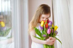 Adorable little girl holding tulips by the window Royalty Free Stock Photography