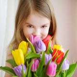 Adorable little girl holding tulips by the window Stock Photos