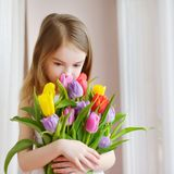 Adorable little girl holding tulips by the window Stock Photography
