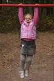 Adorable little girl on horizontal bar royalty free stock image