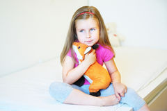 Adorable little girl hugging fox plush toy in bed royalty free stock image