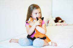 Adorable little girl hugging fox plush toy in bed. At home Stock Photos