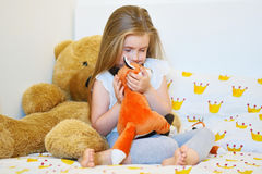 Adorable little girl hugging fox plush toy in bed. At home Royalty Free Stock Images