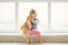 Adorable little girl hugging a teddy bear. Cute baby at home in white room is sitting near window. Stock Photo