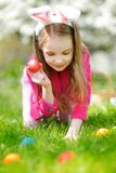 Adorable little girl hunting for easter egg in blooming spring garden on Easter day Royalty Free Stock Photo