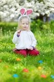 Adorable little girl hunting for easter egg on Easter day Stock Photos