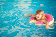 Adorable little girl with inflatable life vest having fun in the pool. Adorable little girl with inflatable life vest having fun, learning to swim in the pool royalty free stock photography