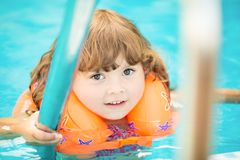 Adorable little girl with inflatable life vest having fun in the pool. Adorable little girl with inflatable life vest having fun, learning to swim in the pool stock photography