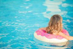 Adorable little girl with inflatable life vest having fun in the pool. Adorable little girl with inflatable life vest having fun, learning to swim in the pool royalty free stock image
