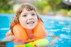 Adorable little girl with inflatable life vest having fun in the pool. Adorable little girl with inflatable life vest having fun, learning to swim in the pool royalty free stock images
