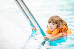 Adorable little girl with inflatable life vest having fun in the pool. Adorable little girl with inflatable life vest having fun, learning to swim in the pool royalty free stock photos