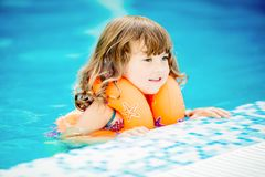 Adorable little girl with inflatable life vest having fun in the pool. Adorable little girl with inflatable life vest having fun, learning to swim in the pool royalty free stock photo
