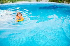 Adorable little girl with inflatable life vest having fun in the pool. Adorable little girl with inflatable life vest having fun, playing with toy in the pool stock photography