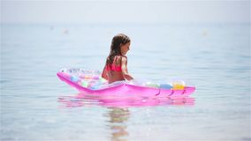 Adorable girl with inflatable mattress in outdoor swimming pool. Adorable little girl with inflatable mattress in the clear sea stock footage