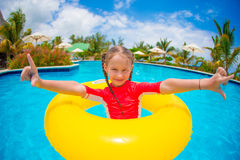 Adorable little girl with inflatable rubber circle during beach vacation. Kid having fun on summer active vacation stock photo